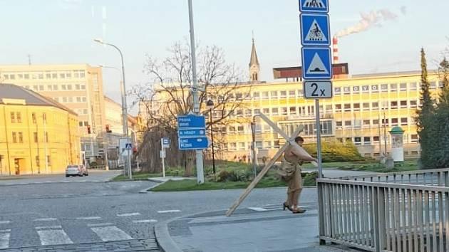 Ulicemi Budějovic prochází záhadný muž s obřím křížem.