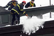 Hasiči odstraňují sníh a rampouchy ze střechy školy.