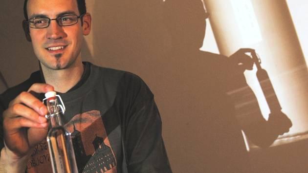 Petr Štumpf ukazuje na snímku upomínkovou lahvičku  s Poněšickou pálenkou.  Společným jednotícím prvkem předmětů  je v několika jazykových mutacích slovo suvenýr a vygravírované či keramické logo města Českých Budějovic.