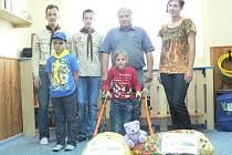 Natálka Petříková (v popředí vpravo) dostala hned dva pěkné dárky. Chodítko z peněz obce jí předal starosta Žáru Miloš Pecháček (nad ní), z víček, která přivezli skauti, plánuje plánuje maminka Jana Petříková koupit sluchátka.