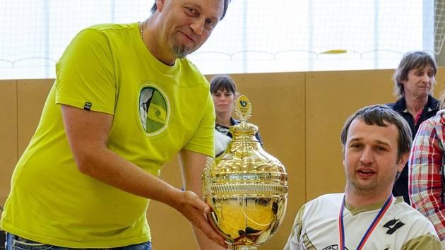 POHÁR pro nejlepší tým extraligy vozíčkářů převzal z rukou předsedy České federace florbalu vozíčkářů Petra Aliny kapitán FBC United František Šindelář (vpravo).
