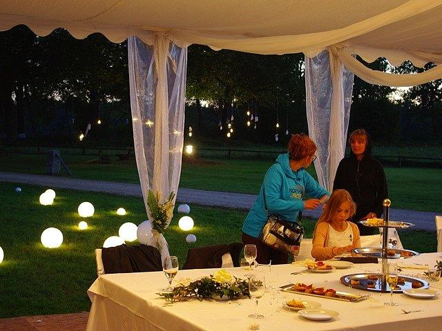 Bílý svatební party stan představuje jednu z vizuálních dominant snímku.