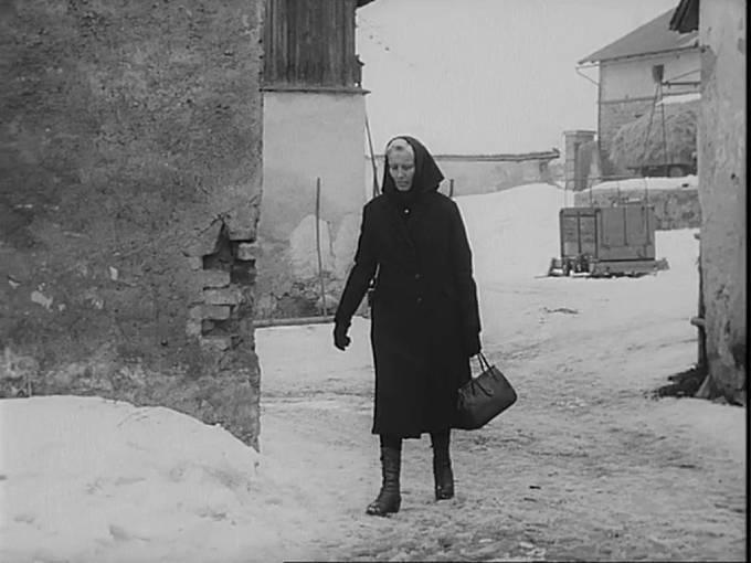 Matylda Chladilová vychází ze statku čp. 89 v Novém Rychnově. Chce získat od úřadů povolení, aby mohla manžela pohřbít ve vsi, odkud musel v době kolektivizace odejít.