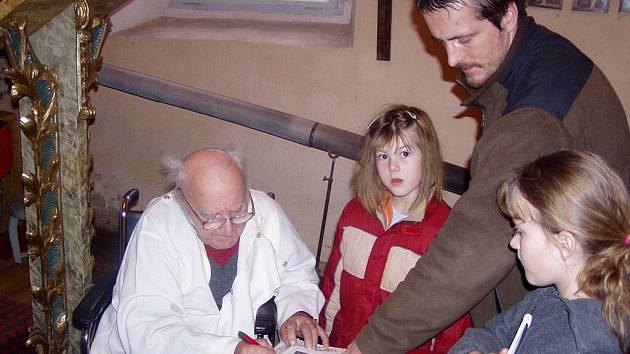 Farář Martin Vích podepisuje čtenářům svou knihou