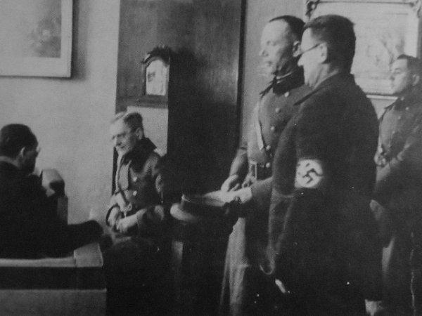Nnacisté přebírají moc na budějovické radnici. Shákovým křížem na rukávu Westen, sedící zády kfotografovi německý radní Friedrich David.