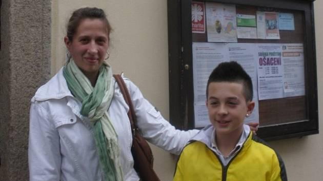 Paní Aušra Bendíková se synem Emilem před domem v budějovické Kanovnické ulici, kde sídlí Diecézní charita.