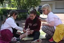 Zraněnou figurantku s tržnou ránou na lýtku ošetřují rudolfovské školačky Barbora Vrtková a Lucie Zasadilová. Na včerejší soutěž mladých zdravotníků se sjelo po čtrnácti týmech z mladší i starší věkové kategorie.