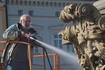 Sochař Ivan Tlášek čistí budějovickou kašnu Samson.