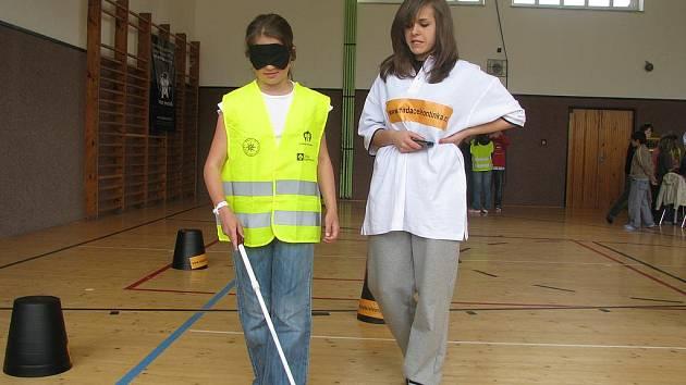 Desetiletá Zuzka Skalová si zkouší chůzi se slepeckou holí na soutěži Neviditelný svět pohybu, která se konala v pondělí  na Základní škole v Pohůrecké ulici.