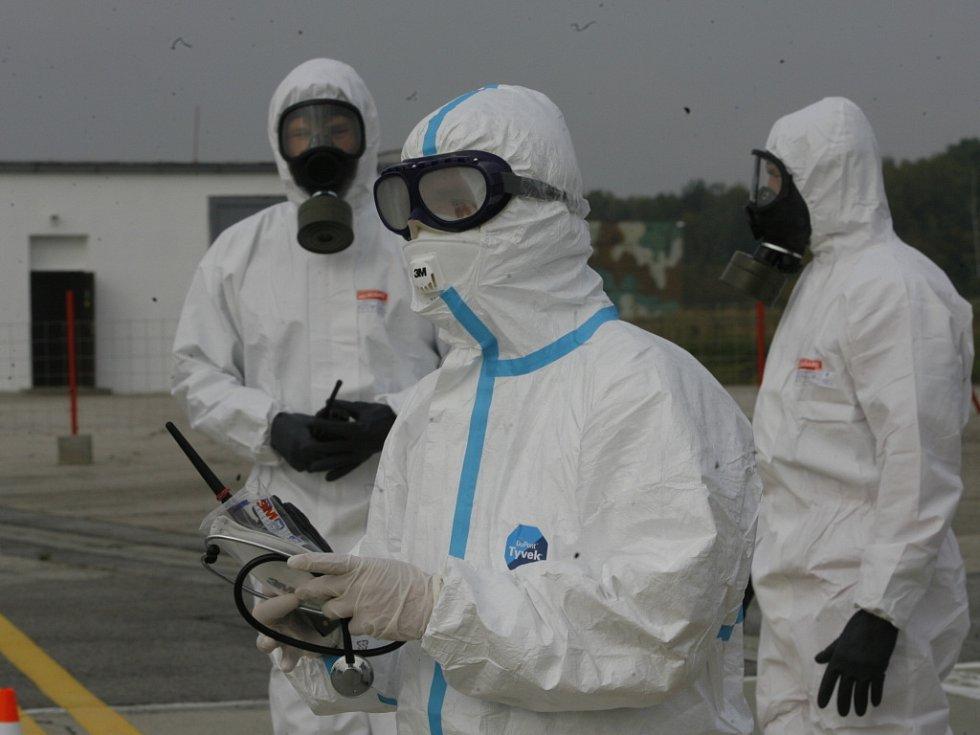 Zdravotník i letištní hasiči v ochranném oděvu těsně před otevřením letadla. V první řadě se musí ujmout nemocného.