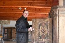 """Malovaný nábytek z regionu patří k zajímavostem vystaveným ve tvrzi Žumberk. Na snímku kastelán Roman Josefík při pravidelném zimním """"provětrávání"""" skříní a truhlic, aby se zbavily vlhkosti."""