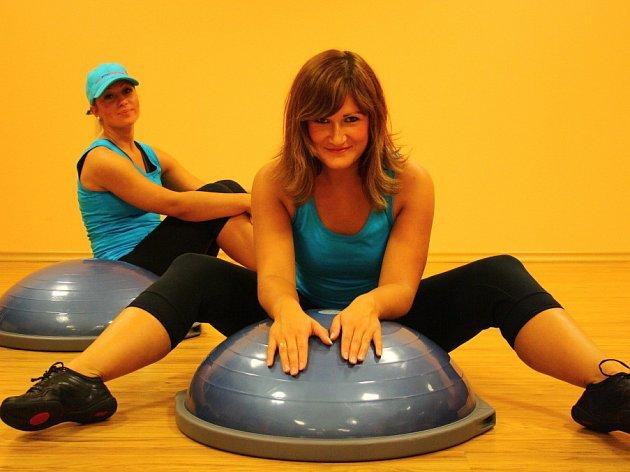 Při cvičení na BOSU komplexně posilujete všechny tělesné partie a navíc zredukujete přebytečný tuk. Něco o tom ví i fitness poradkyně Monika Švárová (v popředí) a Andrea Kopačková.
