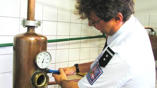 Pracovníci z českobudějovického Celního úřadu při odpečeťování destilačního zařízení v rudolfovské zpracovně ovoce. Na snímku Miroslav Haboň.