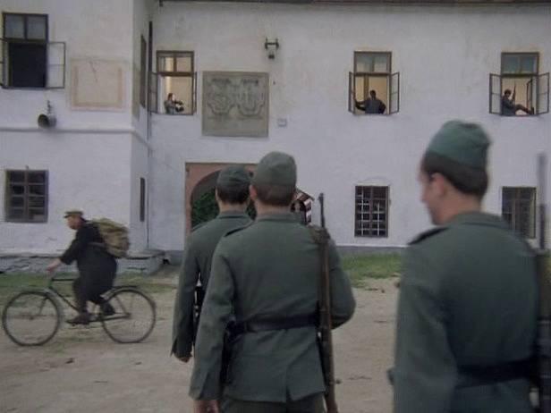 Záběr z filmu Zlatí úhoři. Převozník Prošek (na kole) veze židovské rodině srnčí, které dává sílu. Míjí zámek v Bzí s reliéfy erbů na zdi.