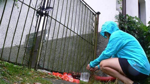U vrat domu v Údolí u Nových Hradů, kde se o víkendu udála rodinná tragédie, lidé nechávají květiny a zapalují svíčky.