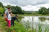 Chytat ryby se děti učí pod dohledem odborníka. Jeden má v ruce prut, druhý pomáhá s podběrákem. Veškeré úlovky končí zase ve vodě.