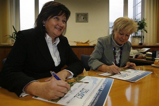 Michaela Čermáková (vlevo) a Ivana Stráská podepisují darovací šek.