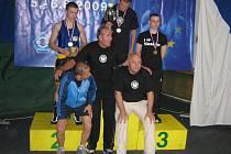 Zdeněk Šesták z Box Clubu Táty Němce v Třeboni na nejvyšším stupínku s druhým Pytlem (vlevo) a třetím Nasirovem, dole jsou Šestákovi kluboví trenéři Zdeněk Musil, Josef Němec a Milan Beneš.