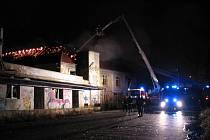 Vysoko šlehající plameny ze střechy bývalé sodovkárny museli profesionální hasiči v noci na pátek likvidovat pomocí výškové techniky.