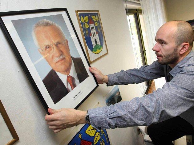 Portrét dosluhujícího prezidenta Václava Klause ve všech školách či úřadech fotografie nové hlavy státu nenahradí. Na zdi tříd či pracoven leckde vyvěsí státní znak.