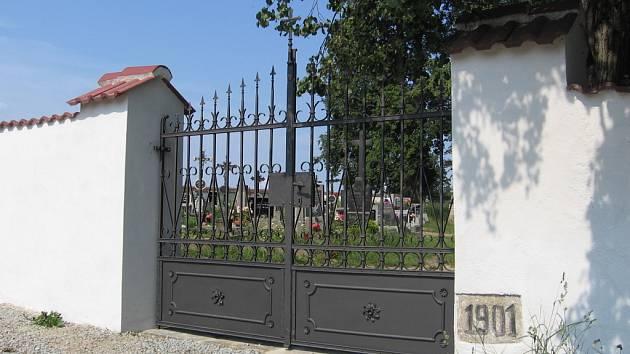Opravená zeď a brána hřbitova.