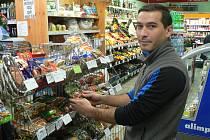 Mandle, vlašské a lískové ořechy, kokos, to je sortiment, který před Vánoci shánějí zákazníci více než jindy. Na snímku jej rovná do regálu Adrian Pintea z malého obchodu na budějovickém Palackého náměstí.