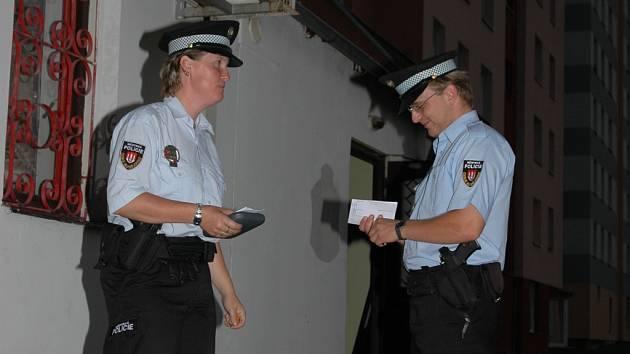 Strážnice a strážník Městské policie v Českých Budějovicích se připravují před jedním z barů na kontrolu nalévání alkoholu mladistvým.  Snímek je z noční akce ze středy.