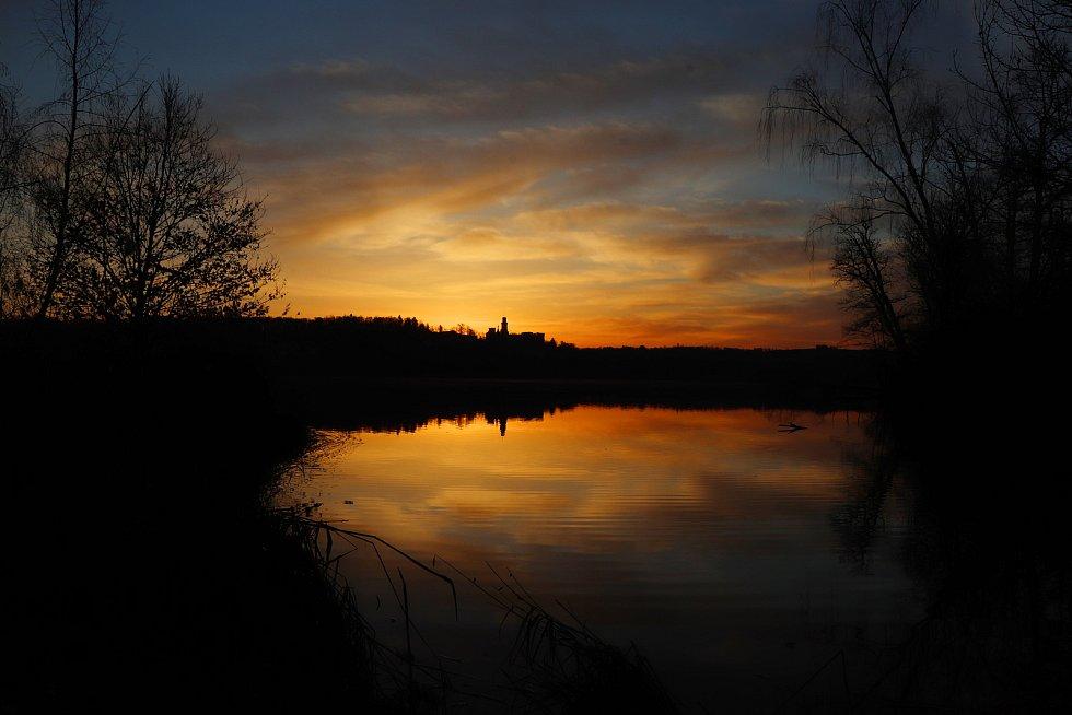 Východ slunce za zámkem Hluboká nad Vltavou přes rybník Munický, který je plný ptactva a romantických zákoutí na hrázi.