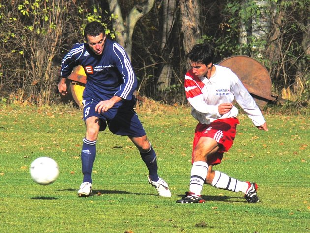 Václav Melichar (v bílém dresu) posílá míč přes bránícího Meidla před branku Týna nad Vltavou. Mariner si doma polepšil o tři body, v dalším kole zajíždí na hřiště táborského lídra.