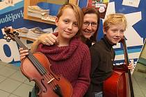 Šťastná jedenáctiletá dvojčata Judita (vlevo) a Agáta Hudečkovy z Černice si v doprovodu maminky Lenky Roskové přišla pro nové hudební nástroje.