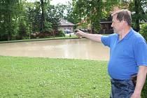 Starosta Jiří Novák ukazuje rybníček, kde se voda přelévala přes hráz.