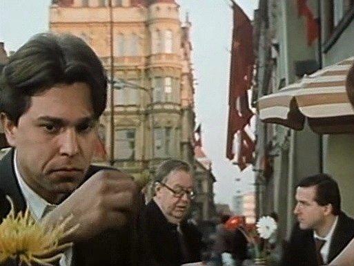 Záběr z filmu Muka obraznosti. Před hotelem Slunce jí Jiří Pomeje. Za ním vlevo sedí českobudějovický pěvec František Kokejl.  Vzadu se rýsuje palác Včela na českobudějovickém náměstí.