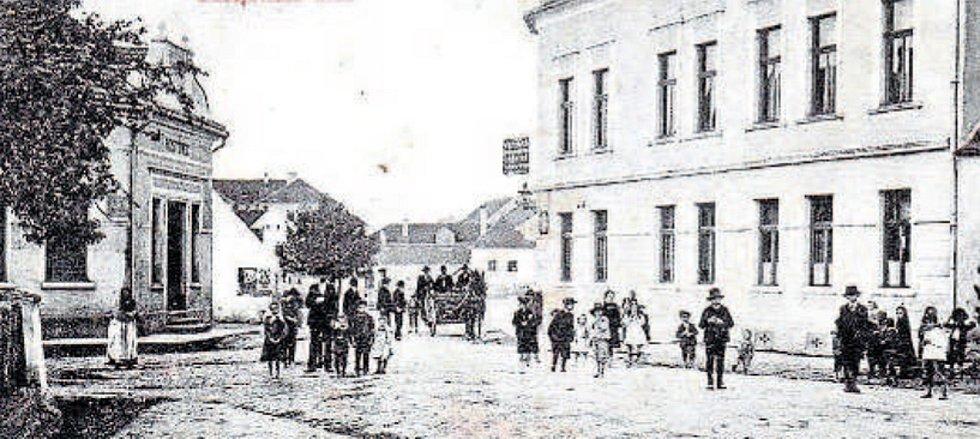 Vjezd do náměstí (okolo 1920). V obou budovách fungovaly kdysi hostince. Vlevo tzv. Němcovský grunt měl výčep od roku 1888, později i obchod.