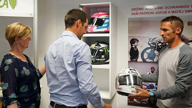 Bratři Jakub (vpravo) a Matěj Smržové slavnostně předávají své závodnické helmy ředitelce Centra Bazalka Vandě Polívkové.