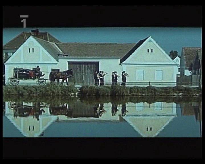Záběr z filmu Srpnová neděle, který se natáčel v Chlumu u Třeboně. Před vozem s rakví kráčí sklářská kapela. Záběr je z dálky přes místní rybníček