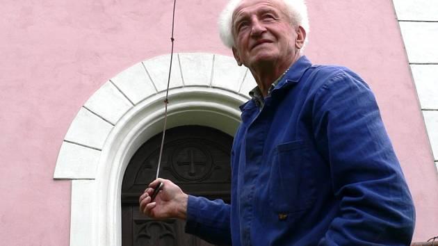 Zvon Břehovské kapličky teď mlčí. Na archivním snímku je  před kapličkou zachycen Václav Fošenbauer s táhlem, pomocí něhož každý den v poledne rozezníval srdce zvonu.