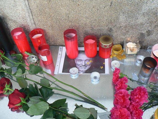 Před českobudějovickou radnicí příznivci legendárního zpěváka Karla Gotta kjeho fotografii pokládají květiny a zapalují uní svíčky.