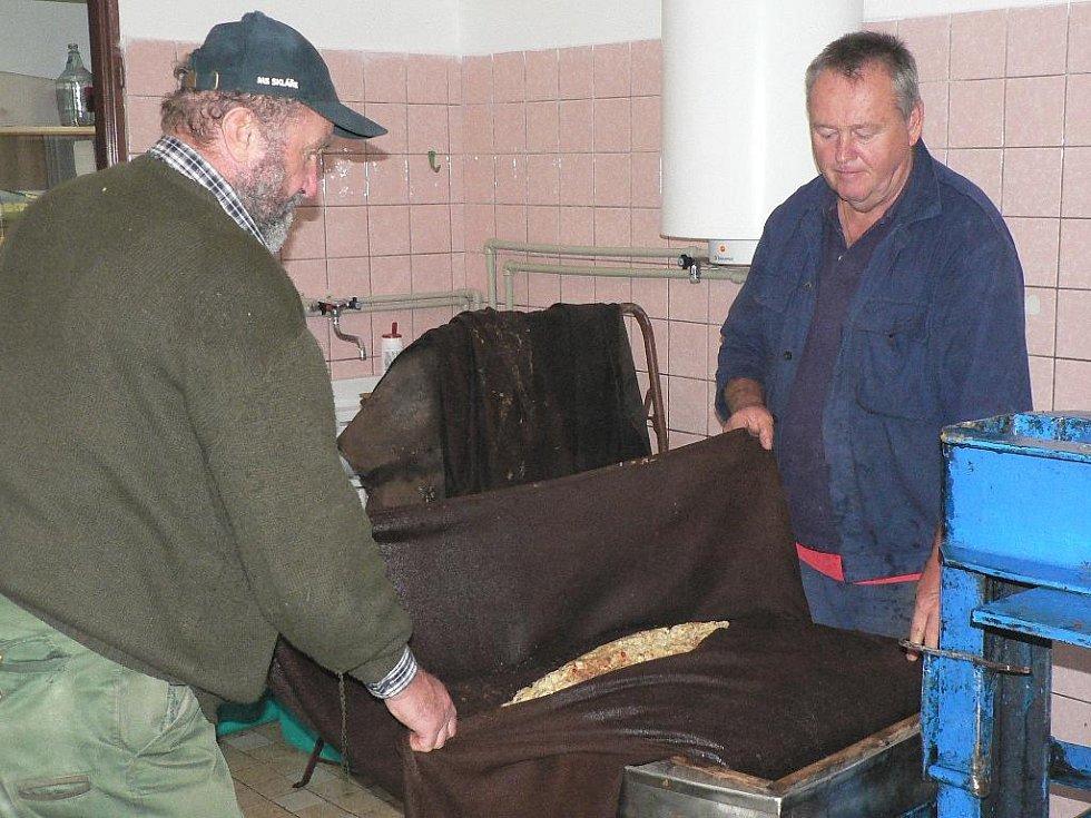 V moštárně zahrádkářů v Nových Hodějovicích už je sezóna v plném proudu. Vojtěch Bíca a Jindřich Houbauer (vpravo) připravují jablečnou drť do lisu.