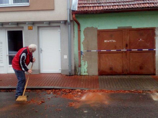 Muž před domem uklízel rozbité tašky ze střechy vČeských Budějovicích vBaarově ulici.