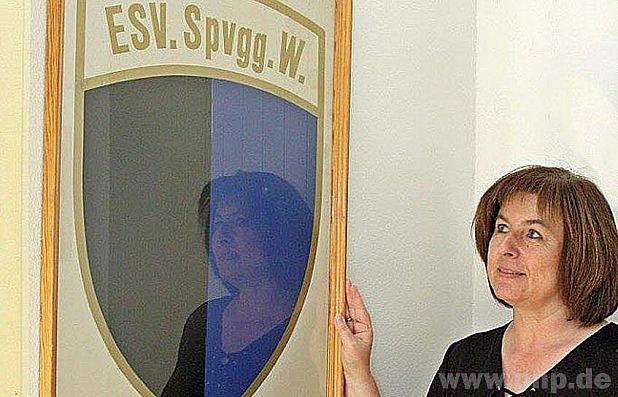 Sekretářka Böhmová před příliš umytou vitrinou.