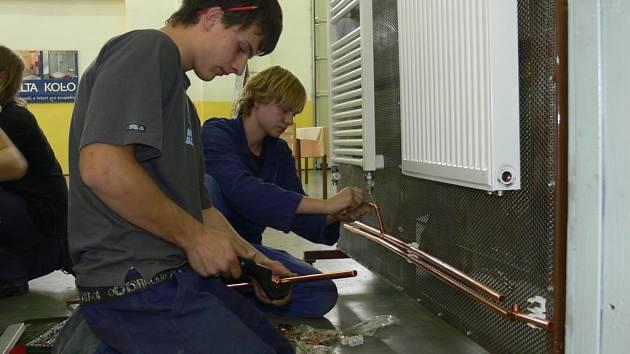 Studenti se učí v hale pro odborný výcvik, jak se zapojuje ústřední topení v koupelně na speciální modelové stěne.
