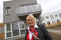 Realitní makléřka Hana Adámková před bývalým hotelem Racek ve Zlivi, přestavěným na byty.