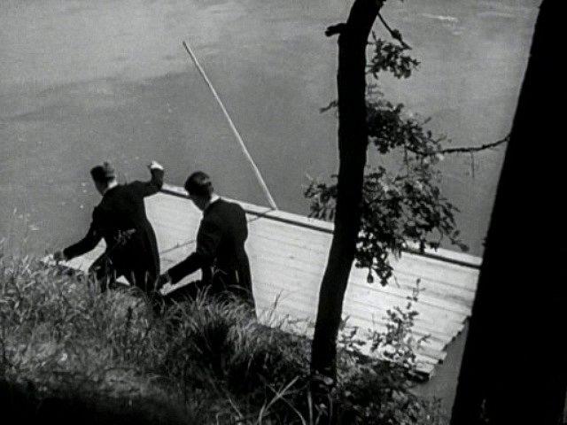 Vzhůru na vor. Herci slézají ve filmu po břehu k vodě a nastupují na dřevěné plavidlo.