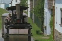 Domková zástavba v osadě Žďárské Chalupy. Na prvním snímku válec přijíždí a silně kouří z komína.