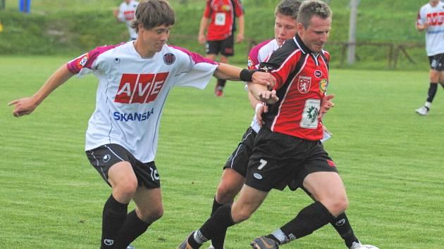 Prachatický Erik Koršala v přípravě s juniorkou Dynama na Složišti (1:1) vyváží míč, Ladislav Nekvinda ho ale stíhá.