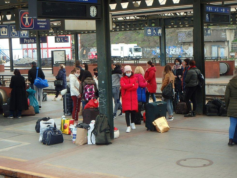 Na pražském nádraží čekají lidé na své spoje disciplinovaně s rouškami.