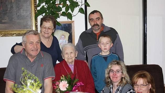 Stoletá Marta Trupelová (uprostřed) žije ve Strážkovicích s dcerou Marií Karvánkovou (druhá zleva ) a její rodinou. Pravnuk Jan Dvořák mladší (vpravo vedle jubilantky) se narodil 8. března 2004, o 90 let a jeden den později, než oslavenkyně.