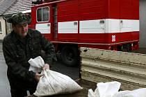 Plno práce mají po přívalových deštích profesionální i dobrovolní hasiči. Snímek je z pytlování v Husinci.