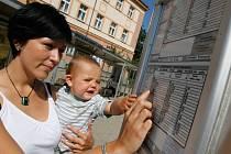 Veronika Schelová se svým dvouletým synem Maxem sleduje jízdní řád městské hromadné dopravy v Českých Budějovicích na zastávce Senovážné náměstí – pošta.