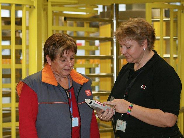Členka ostrahy Marika Kohoutková vyzývá pracovnici vstupující do elektrárny k provedení dechové zkoušky. Tato kontrola byla stejně jako drtivá většina ostatních negativní.
